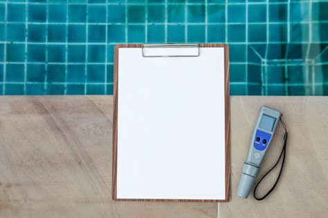 blank white paper on clipboard on the side of inground pool next to a digital water tester