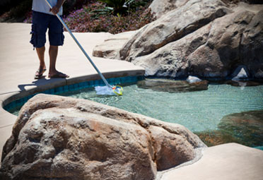 man dipping a skimmer into an in-ground pool