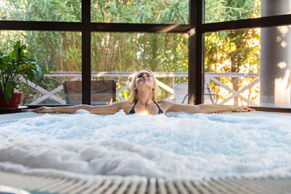 woman soaking in a luxurious, bubbly hot tub