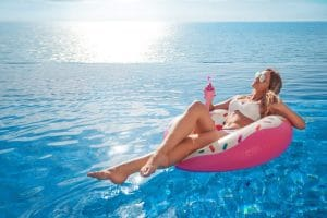 female in bikini at the swimming pool with drink laying on an inflatable pool float