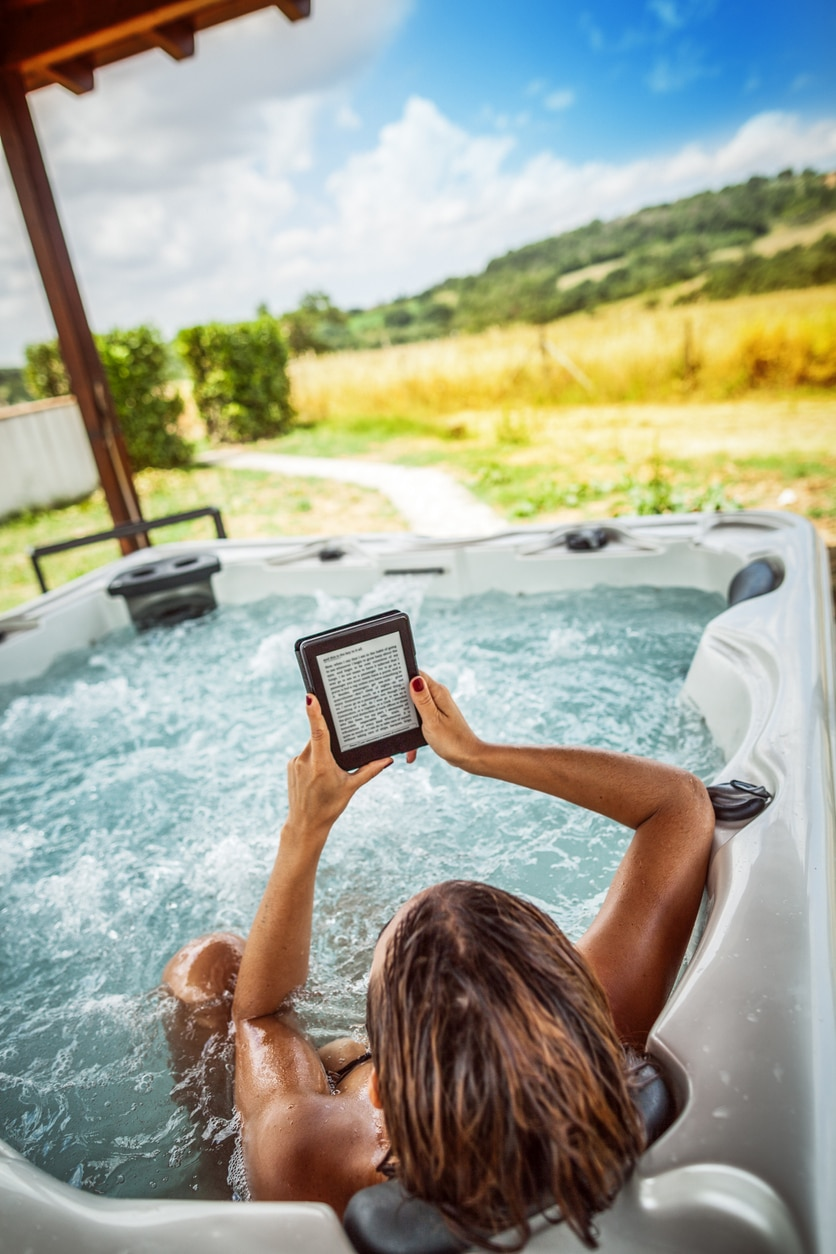 young woman relaxing in a hot tub reading an electronic book