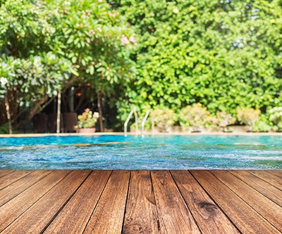 above ground pool with a deck in a beautifully landscaped backyard